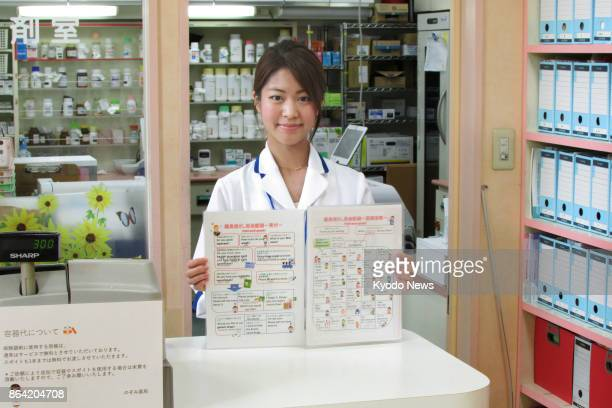 Haruka Hirose a pharmacist at Nozomi pharmacy in Tokyo's Koto Ward on Sept 5 2017 shows a pointandspeak conversation notebook that she compiled for...