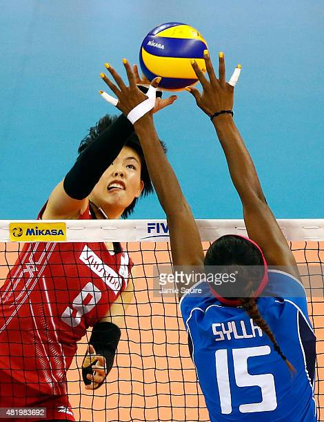 Haruyo Shimamura of Japan tips the ball over the net as Miriam Fatime Sylla of Italy blocks during the final round match on day 4 of the FIVB...