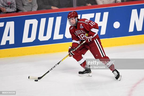Harvard Crimson defenseman Adam Fox controls the puck during an NCAA Frozen Four semifinal game with the Harvard Crimson and the MinnesotaDuluth...