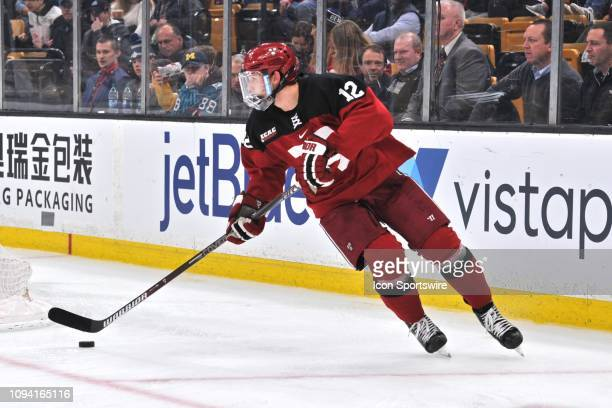 Harvard Crimson defenseman John Marino brings the puck out from behind the net During the Harvard Crimson game against the Boston College Eagles on...