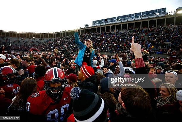 Harvard Crimson fans celebrate after rushing the field following their 3124 win against the Yale Bulldogs at Harvard Stadium in their 131st meeting...