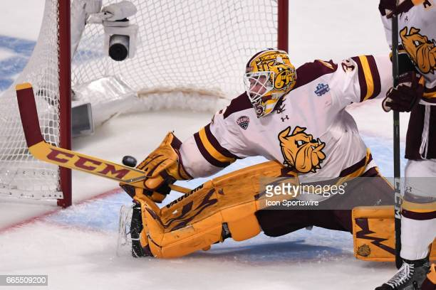 Harvard Crimson forward Tyler Moy scores against MinnesotaDuluth Bulldogs goalie Hunter Miska in the first period of an NCAA Frozen Four semifinal...