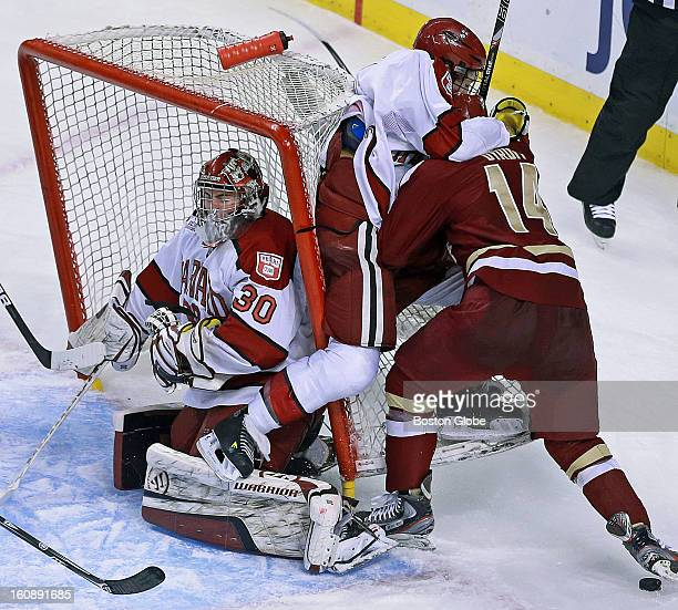 Harvard goalie Raphael Girard has the cage fall on to him during a second period crashing of the net. Harvard University met Boston College in the...