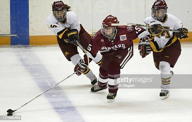 Harvard Katie Johnston center tries to take the puck away from Minnesota's Chelsea Brodt left and Melissa Coulombe right during the first period of...