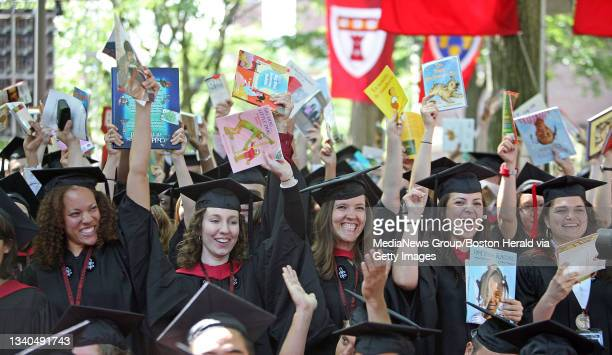 Harvard School of Education students hold up their summer reading material after being conferred at the Harvard University Commencement in Harvard...
