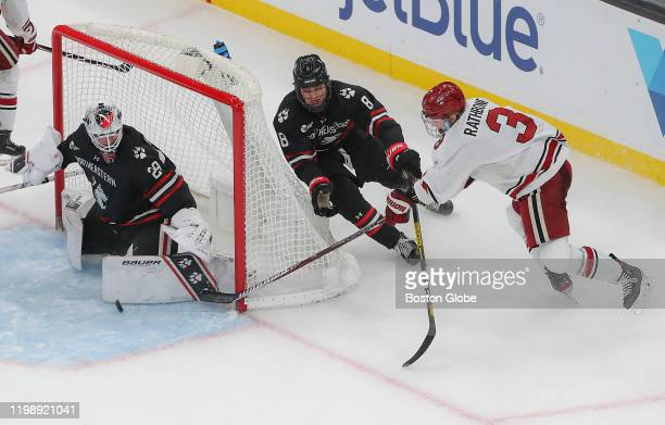Harvard University Crimson defenseman Jack Rathbone wrap around shot denied by Northeastern University Huskies goaltender Craig Pantano and...