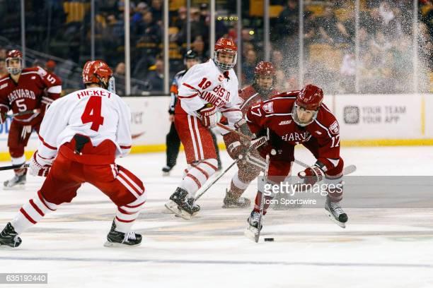 Harvard University Crimson forward Sean Malone kicks up ices shards to skate past Boston University Terriers forward Clayton Keller and defenseman...
