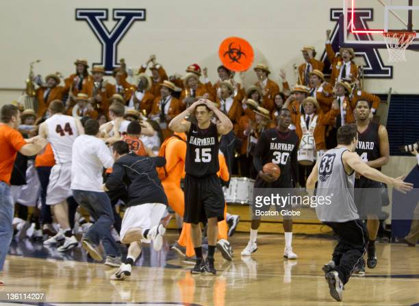 Harvard University players left to right Christian Webster #15 Kyle Casey #30 and Keith Wright #44 walk off the court in disbelief after Princeton's...