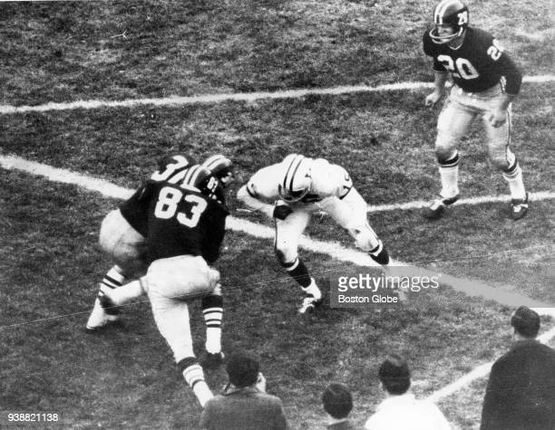 Harvard University's Bruce Freeman tries to run around a teammate and a Yale player and into the end zone after catching a pass during the final 42...