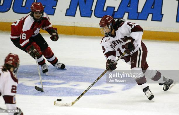 Harvard's Julie Chu, right tries to keep the puck away from St. Lawrence's Whitney Carbone, left, during the NCAA 2004 Women's Frozen Four at the...