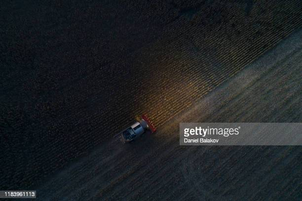 harvest season. aerial view of a combine harvester gathering the corn crop in the agricultiral field after sunset in autumn. agricultural equipment in cultivated land. nighttime. working late. - corn crop stock pictures, royalty-free photos & images