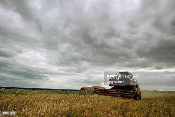 A harvester works a field in the village of NurShari 900 kilometers east of Moscow August 18 2002 in MariEl an autonomous republic of the Russian...