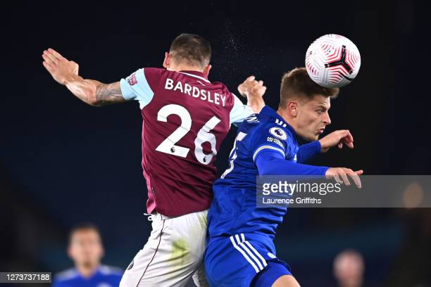 Harvey Barnes of Leicester City and Phil Bardsley of Burnley compete for a header during the Premier League match between Leicester City and Burnley...