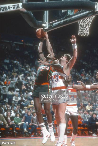 Harvey Catchings of the Milwaukee Bucks grabs a rebound over Jeff Ruland of the Washington Bullets during an NBA basketball game circa 1983 at the...