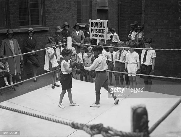 Harvey Christian Rupert Peter Combe boxing with John Herbert at a children's garden party in aid of the Duchess of York's Maternity Clinic in the...