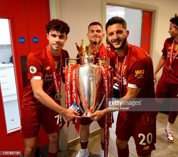 Harvey Elliott, Neco Williams and Adam Lallana of Liverpool in the dressing room with the premier league trophy in the dressing room after winning...