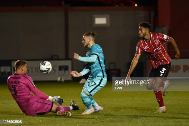Harvey Elliott of Liverpool attempts to beat Alex Palmer of Lincoln City to the ball during the Carabao Cup third round match between Lincoln City...