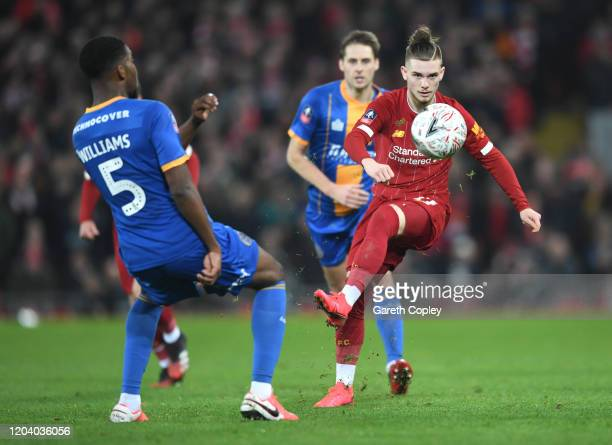Harvey Elliott of Liverpool is challenged by RoShaun Williams of Shrewsbury Town during the FA Cup Fourth Round Replay match between Liverpool FC and...