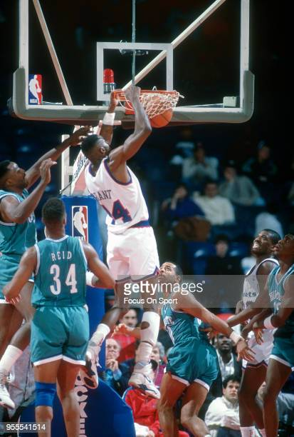 Harvey Grant of the Washington Bullets slam dunks against the Charlotte Hornets during an NBA basketball game circa 1991 at the Capital Centre in...