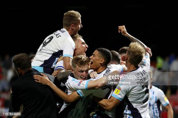 Harvey Knibbs of Cambridge United celebrates with teammates after scoring their winning penalty following a penalty shootout in the Carabao Cup First...