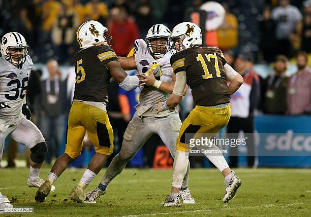 Harvey Langi puts pressure on Wyoming Josh Allen during the San Diego Credit Union Poinsettia Bowl game between the BYU Cougars and the Wyoming...