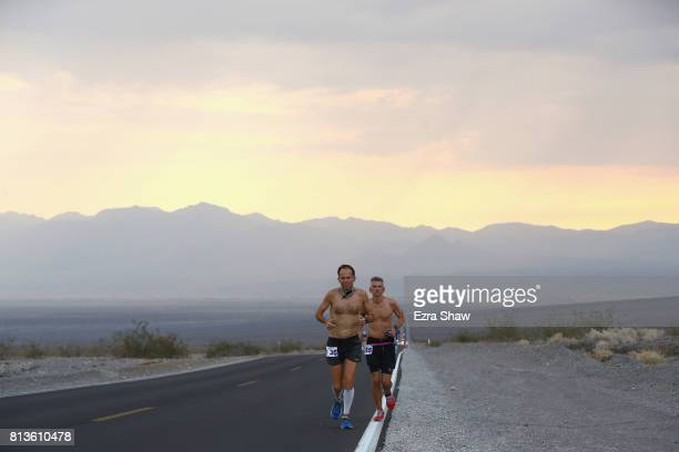 Harvey Lewis III runs with a member of his support crew during the STYR Labs Badwater 135 on July 12 2017 in Death Valley California The start of the...