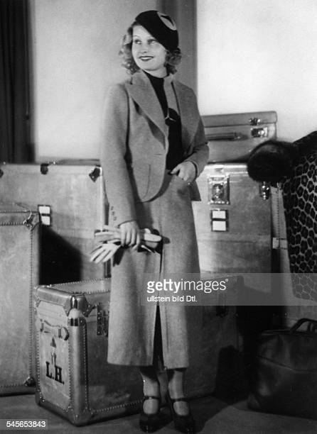 'Harvey Lilian Actress Germany / Great Britain*wearing a beige Homespun ladies'suit a jumper and cap with Mercedes star design Joe Strassner...