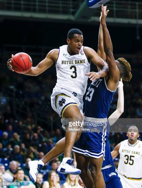 J Harvey of the Notre Dame Fighting Irish passes the ball against Greg Alexander of the Mount St Mary's Mountaineers defends at Purcell Pavilion on...