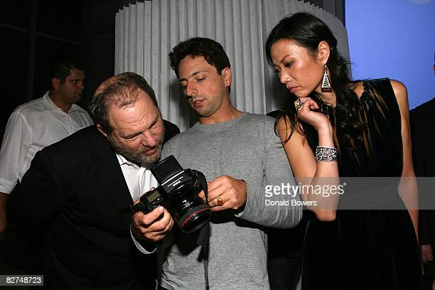 Harvey Weinstein reviews Sergey Brins photography as Wendi Deng looks on during the 23 and Me Spit party at the IAC Building on September 9 2008 in...