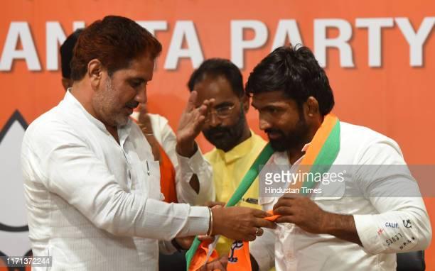 Haryana president Subhash Barala felicitates Olympic bronze medalist Yogeshwar Dutt after he joined BJP, at BJP headquarter on September 26, 2019 in...