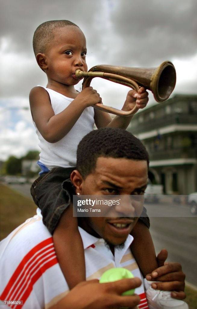 Hasaan Goffner plays a trumpet as Ersel Bogen holds him while watching the Satchmo SummerFest Second Line Parade August 6, 2006 in New Orleans, Louisiana. The festival honors jazz great Louis 'Satchmo' Armstrong and was moved this year to the French market area in the French Quarter from the Old U.S. Mint where it has been held in the past due to damage from Hurricane Katrina.