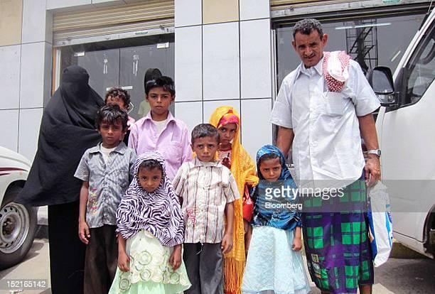 Hasan Abdullah Quanas a Yemeni fisherman right poses with Najibah Ahmed Bahri widow of murdered fisherman Mohammed Ali Quanas left and their children...