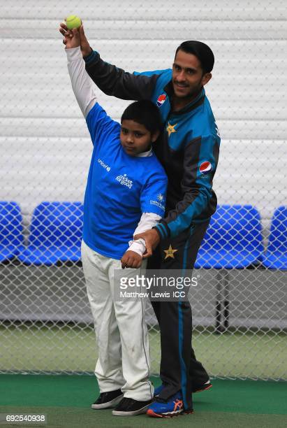 Hasan Ali of Pakistan shows a young school child how to bowl during an ICC Champions Trophy Cricket for Good clinic at Edgbaston on June 5 2017 in...