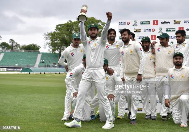 Hasan Ali walks off with the trophy as the Pakistan cricket team pose for a team photograph after defeating Ireland on the fifth day of the...