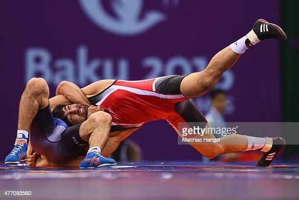 Hasan Aliyev of Azerbaijan and Migran Arutyunyan of Armenia compete in the Men's Wrestling 66kg Greco Roman semi finals during day two of the Baku...