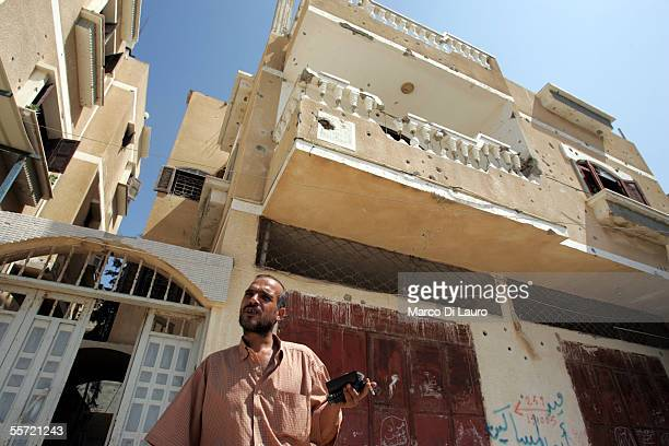 Hasan Kishta 39yearsold stands in front of his bullet hole scarred house on September 19 2005 in Rafah refugee camp Gaza Strip Hasan Iman and their...