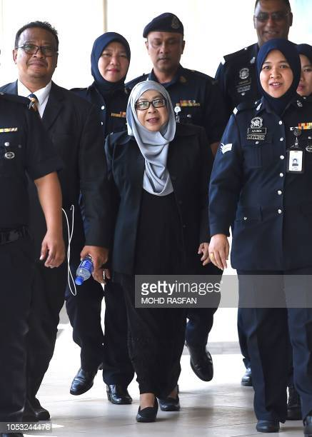 Hasanah Abdul Hamid the former head of a shadowy spy agency which worked directly under former Malaysia's prime minister Najib Razak is escorted by...