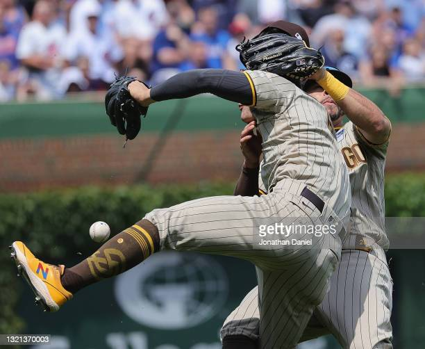 Ha-Seong Kim and Tommy Pham of the San Diego Padres collide going for a fly ball in the 4th inning against the Chicago Cubs at Wrigley Field on June...