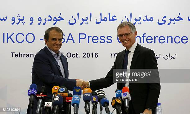 Hashem YekkehZareh the CEO of industrial group Iran Khodro and the head of French car manufacturing giant PSA group Carlos Tavares shake hands...