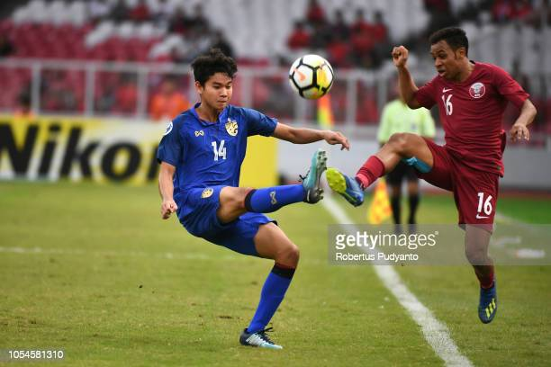 Hashim Ali A Ali of Qatar and Munjit Sarawut of Thailand fight for the ball during the AFC U19 Championship Indonesia quarter final match between...