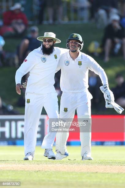 Hashim Amla and Quinton de Kock of South Africa celebrate the dismissal of Henry Nicholls of New Zealand during day two of the First Test match...