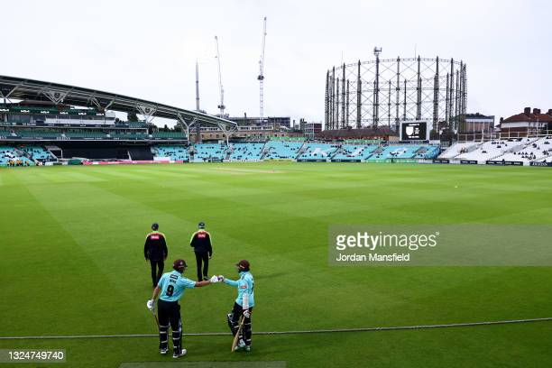 Hashim Amla and Will Jacks of Surrey punch gloves as they make their way to the field to open the batting during the Vitality T20 Blast match between...