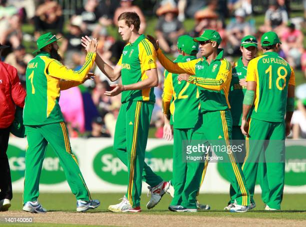 Hashim Amla of South Africa congratulates teammate Morne Morkel on the wicket of Tim Southee of New Zealand during the One Day International match...