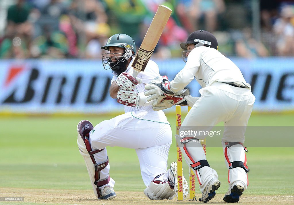 Hashim Amla of South Africa sweeps a delivery during day one of the second test match between South Africa and New Zealand at Axxess St Georges on January 11, 2013 in Port Elizabeth, South Africa.