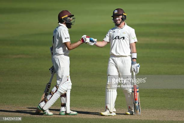 Hashim Amla of Surrey and Ollie Pope celebrate reaching their 300 partnership on day four during the LV= Insurance County Championship match between...