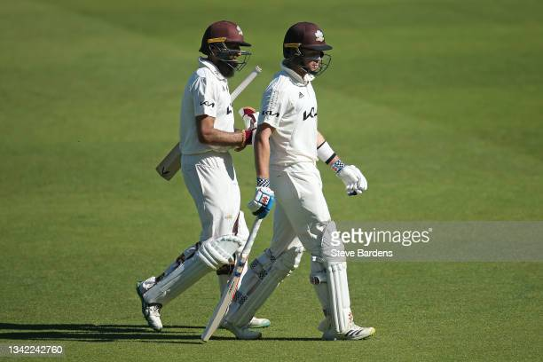 Hashim Amla of Surrey and Ollie Pope leave the pitch for the lunch interval after reaching their 300 partnership on day four during the LV= Insurance...