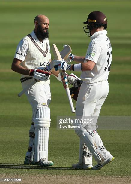 Hashim Amla of Surrey celebrates reaching his century with Ollie Pope on day four during the LV= Insurance County Championship match between Surrey...
