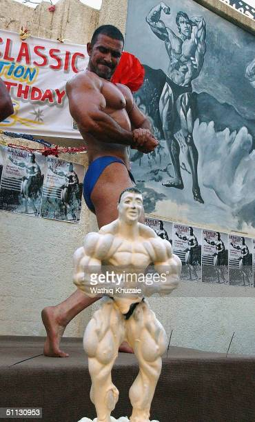 Hashim Muhsin performs his best flex near posters of Arnold Schwarzenegger during a body building competition at Arnold Classic gym on July 30 2004...