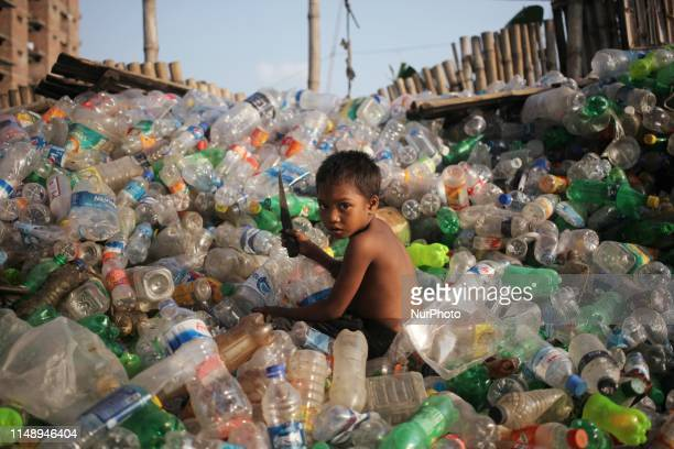 Hashin , reacts to the camera as he working in a plastic bottles recycling factory in Dhaka, Bangladesh on Monday 10 June 2019. There are many...
