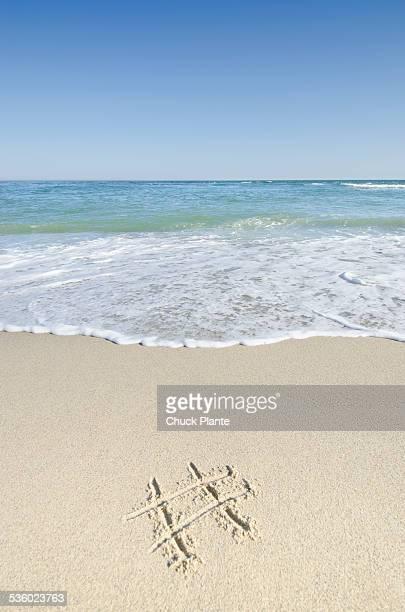 Hashtag symbol drawn on sandy beach